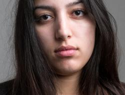 Stern young woman looks into camera.