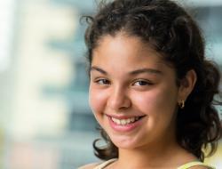 Mujer joven sonríe a la cámara