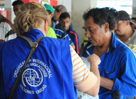 IOM official provides support to migrants lining up for supplies