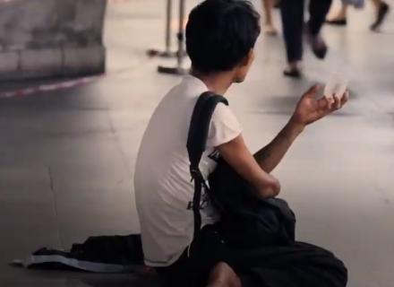 Persona adulta sentada en una calle solicitando dinero