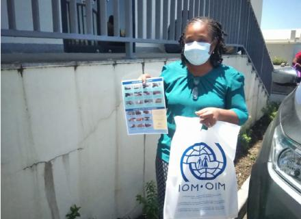 Woman wearing medical mask holds information poster on COVID-19 and IOM donation bag