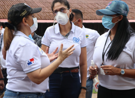 Mujeres con mascarilla conversan. Sus camisetas tienen logos de la OIM y el gobierno de Panamá.