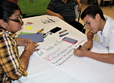 Young students engage in collaborative activity to create a community information campaign