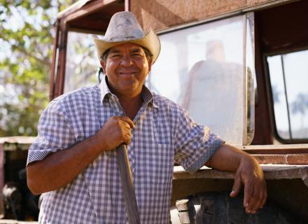 Foto ilustrativa de hombre con sombrero junto a camión.