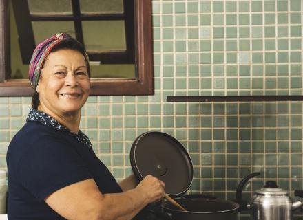 Foto ilustrativa de mujer mayor laborando en una cocina, lavando platos.