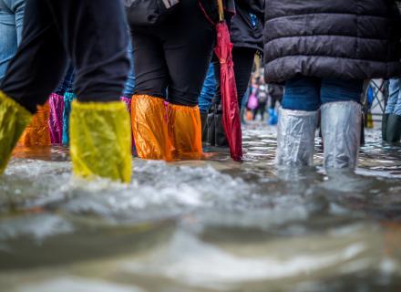 Pies cubiertos por bolsas plásticas durante crisis de inundación