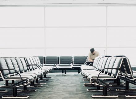 Sala de abordaje en aeropuerto casi vacía. Solamente aparece una persona, a la distancia.
