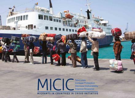 Fila de personas cargan bultos junto a un barco. Esperan para abordar.
