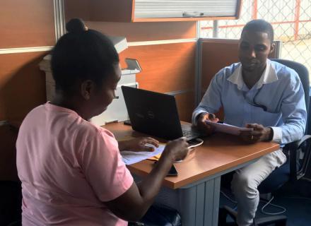 Persona sentada tras escritorio escribe en computadora mientras atiende a persona migrante.