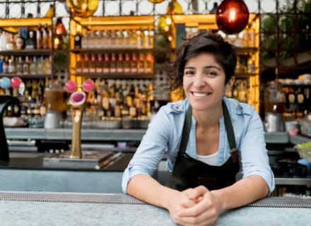 Mujer con delantal atiende pequeño negocio.
