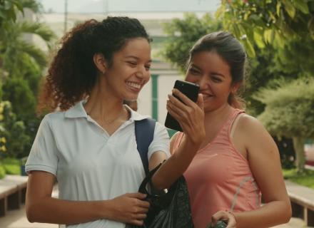 Dos mujeres jóvenes sonríen mientras observan un teléfono celular
