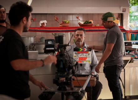 Fotografía del proceso de producción de un video. Hombre sentado en una cocina ve directamente a la cámara.