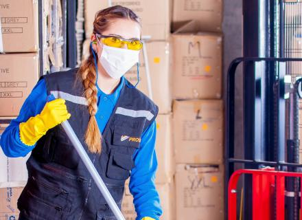 Adult employee wearing personal protection equipment cleans warehouse