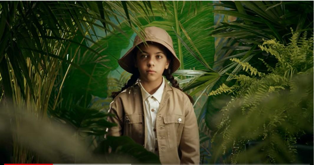 Niña con traje de safari rodeada de la jungla